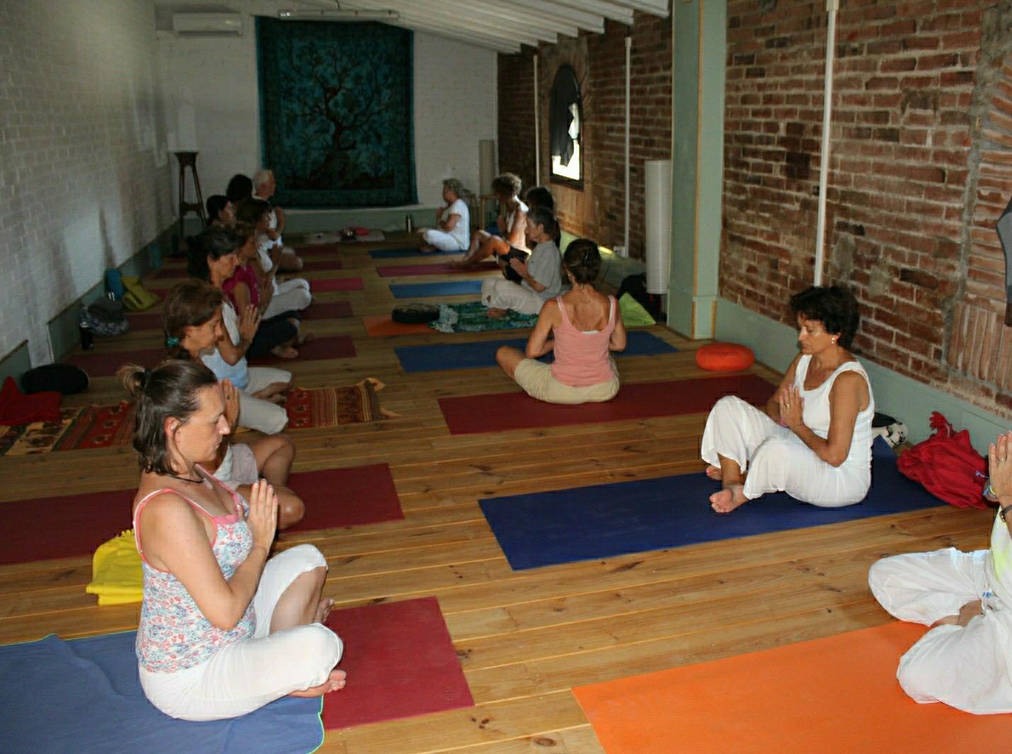 Personas meditando en clase de yoga