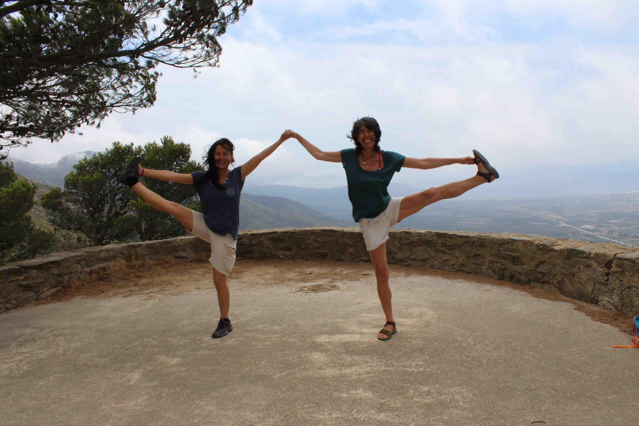 Dos profesoras de yoga en equilibrio en la naturaleza